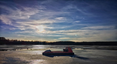 Hovercraft resting on frozen lake after icefishing